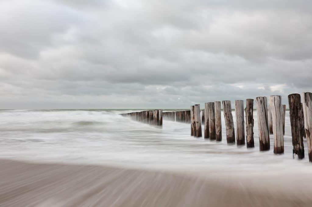 Mooie foto aan de kust, met ondergelopen palen door de zee