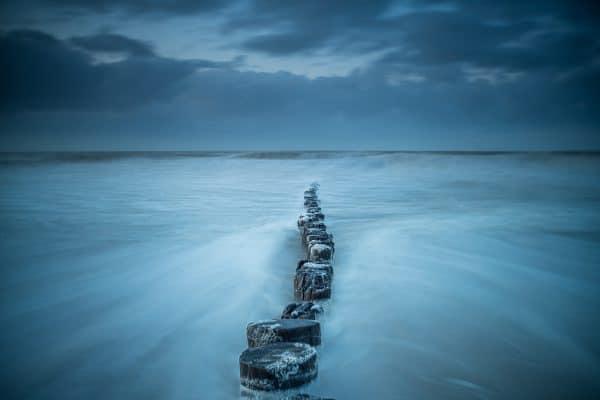 Super mooie foto van palen en de zee met een hele mooie blauwe tint