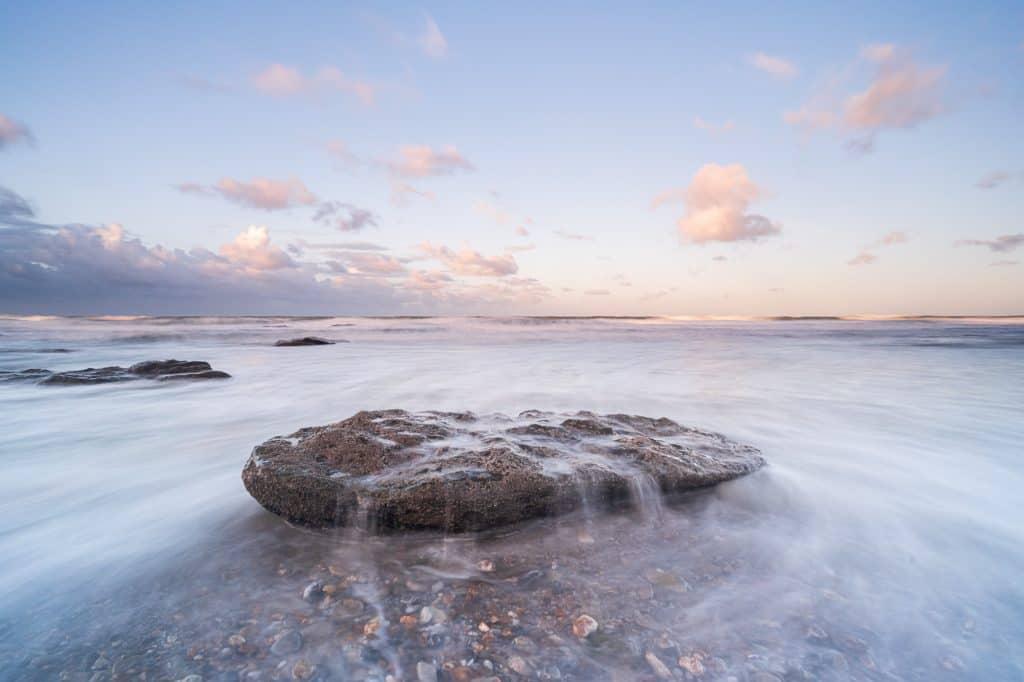Mooie foto van een rots en de zee heeft een soort van rookachtig gordijn door de NiSi filter