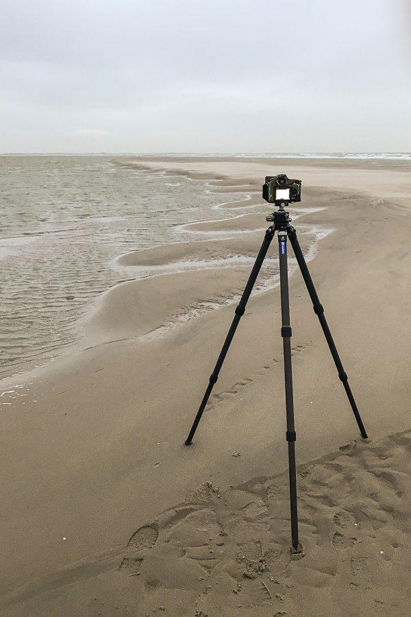 Leostatief inclusief camera op het strand tijdens eb